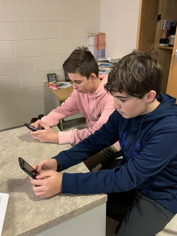 Matthew Willar '22 and Owen Kelly '21 play Mario Kart Tour on their phones.