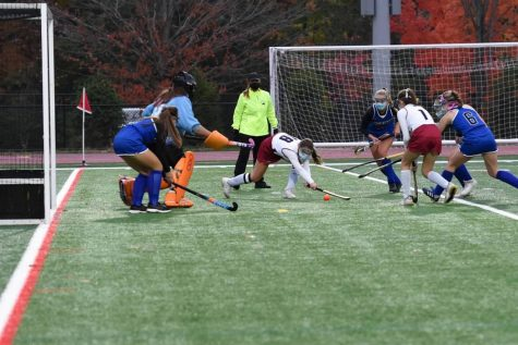 #18 Senior Captain Julia French uses a reverse sweep to shoot on Leominster goal keeper. Trailed by Freshman #1 Cayla Erlich.