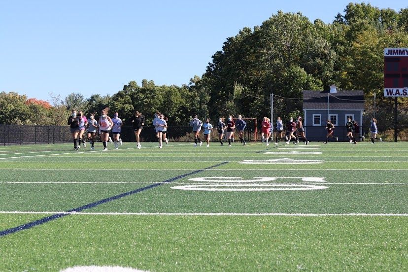 WHS Field Hockey running a socially distanced warm up lap